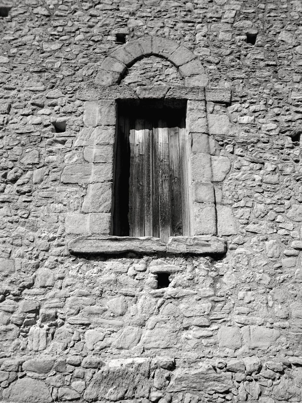 LOW ANGLE VIEW OF WINDOW ON OLD WALL OF BUILDING