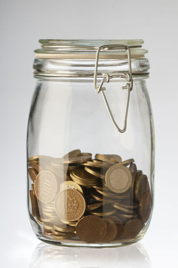 Close-up of coins in jar against white background