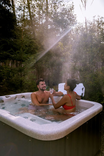 Couple sitting in hot tub in forest