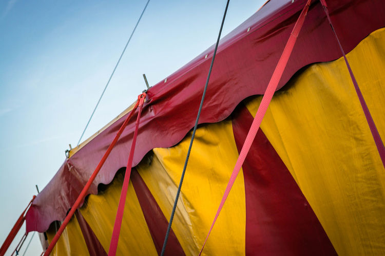 Circus Blue Clear Sky Close-up Clothing Day Environment Flag Hanging Low Angle View Multi Colored Nature No People Outdoors Pride Red Sky Sunlight Textile Wind Yellow