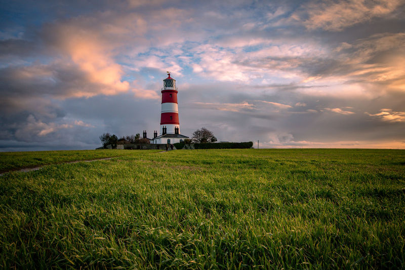 Lighthouse on field against sky at sunset