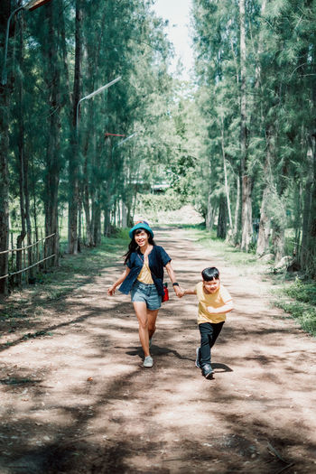 Full length of woman and son running on road amidst trees in forest
