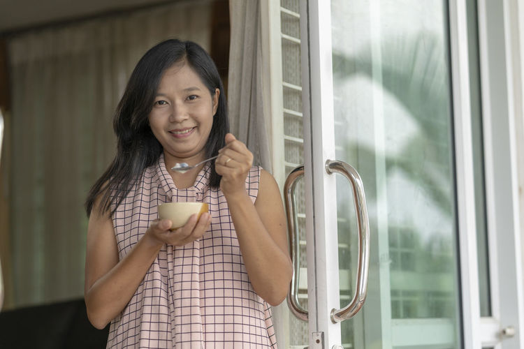 Portrait of smiling mid adult woman eating food while standing by window at home