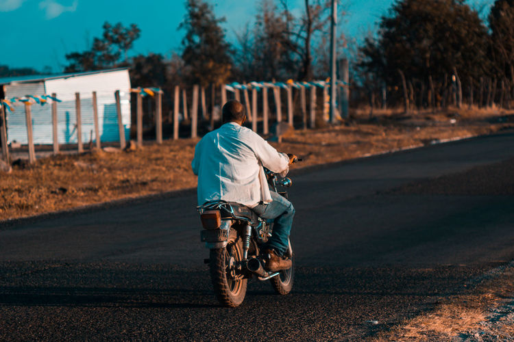 Rear view of man riding motorcycle on road