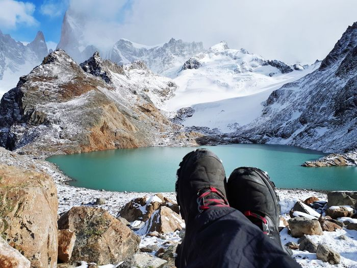 Low Section Of Person Sitting Against Lake And Snowcapped Mountains During Winter