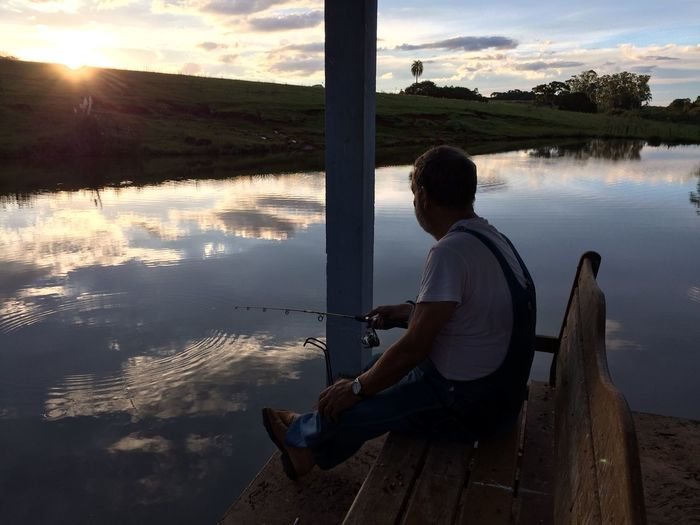 Side view of man sitting on bench while fishing in lake during sunset
