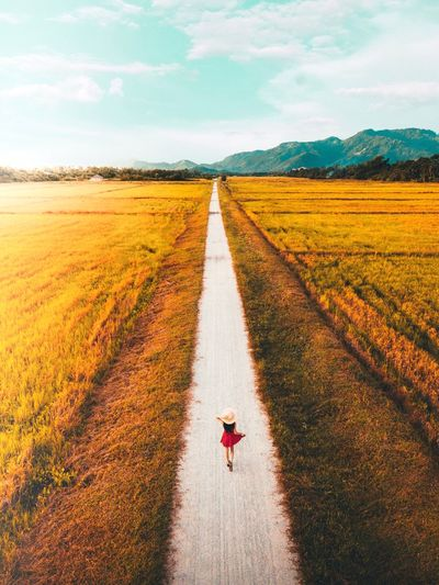 High angle view of woman walking on road amidst field against sky
