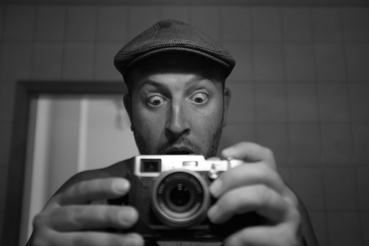 Portrait of shocked mature man photographing with camera