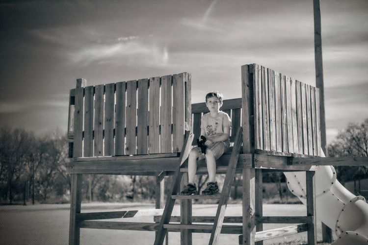 Boy Sitting On Wooden Built Structure At Playground