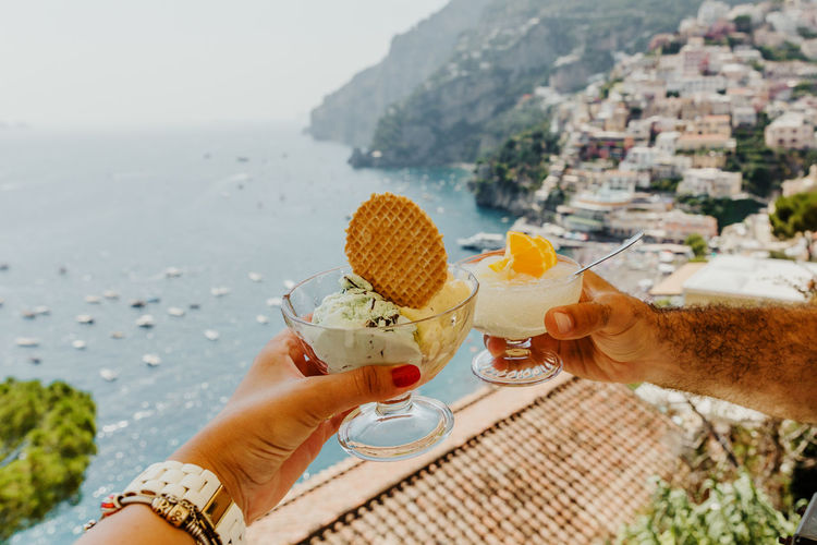 Midsection of person holding ice cream against sea