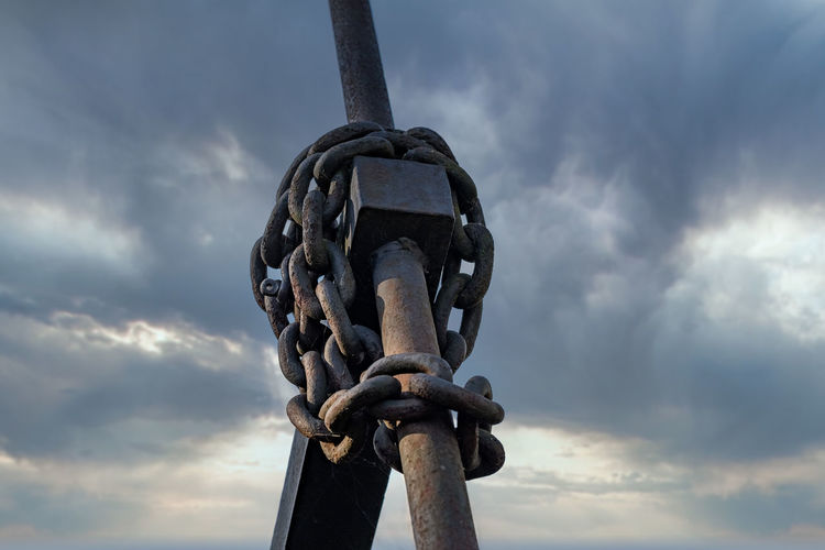Low angle view of rusty chain against sky