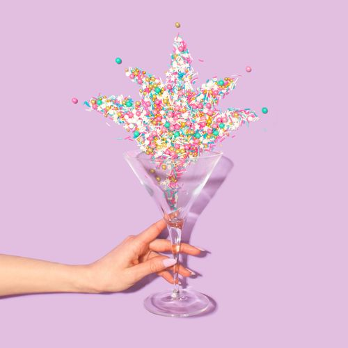 Optical illusion of woman holding drinking glass with sprinkles over purple background