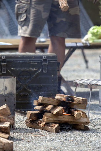 Burning firewood by camping stove against man standing on field during camping