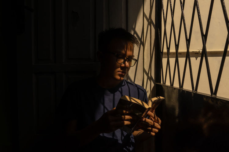 Young man reading book while sitting by gate