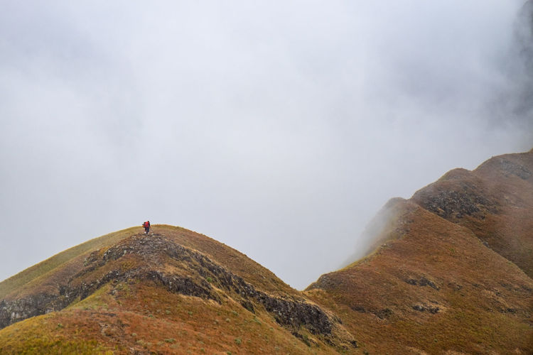 Scenic view of a hiker on mountain ridge in heavy fog