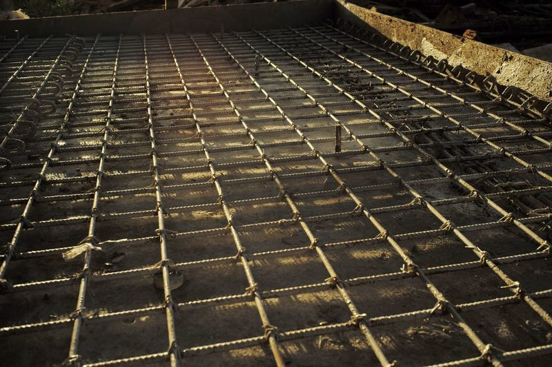 Reinforcement steel for the concrete floor with the light of sunset Building Ground Metal Foundation Grid Wire Rod Iron Reinforcement Steel Building Construction Structure Engineering Architecture Material Pattern Footpath No People High Angle View Street Day Full Frame In A Row Outdoors Paving Stone Sunlight Backgrounds Arrangement