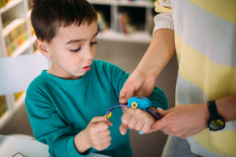 Mom gives her son his first watch. learning to determine the time by the clock.