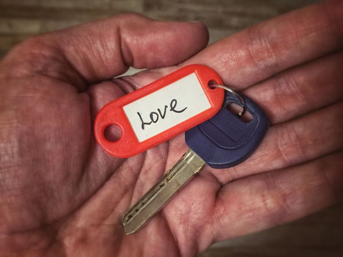 Cropped hand with key ring with love text