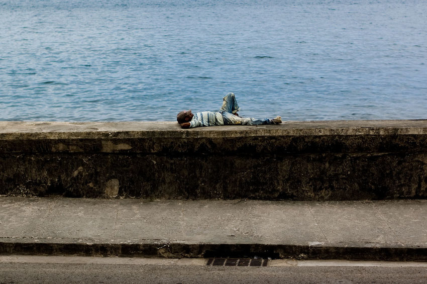 A man sitting on the retaining wall by the sea Blue Cuba Day El Malecon Grass Livestock Man Nature Outdoors Photoful Relaxation Sea Side View Sleeping Water