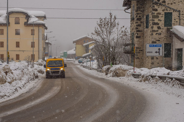 Cars on street by buildings in city during winter