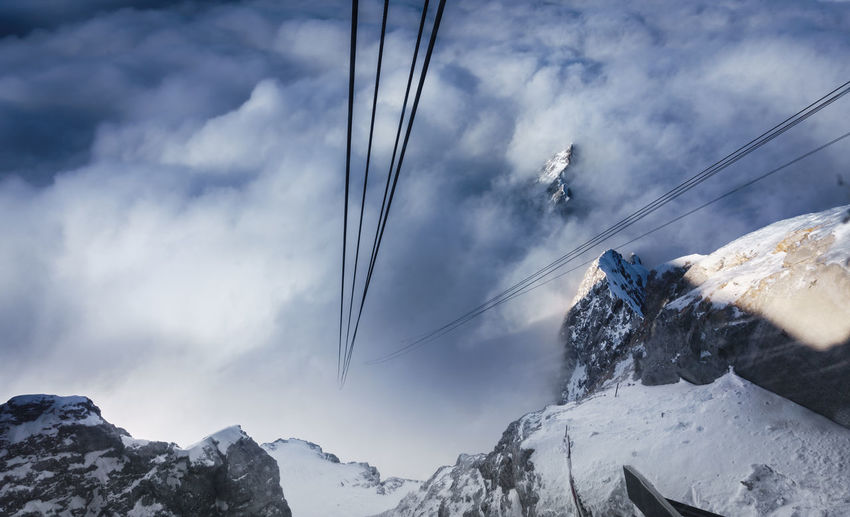 High Angle View Of Steel Cables Over Snowcapped Mountains In Foggy Weather