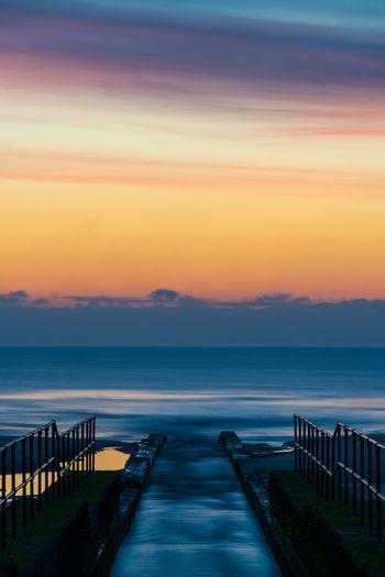 Pier over sea against sky during sunrise