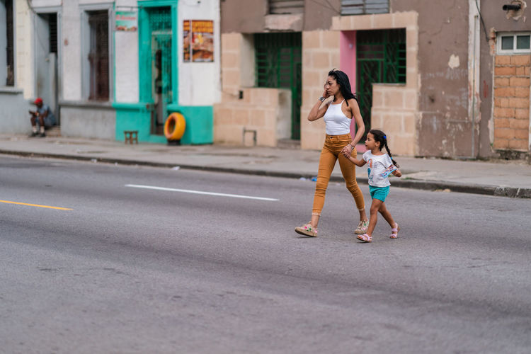 Full length of mother and daughter on road in city