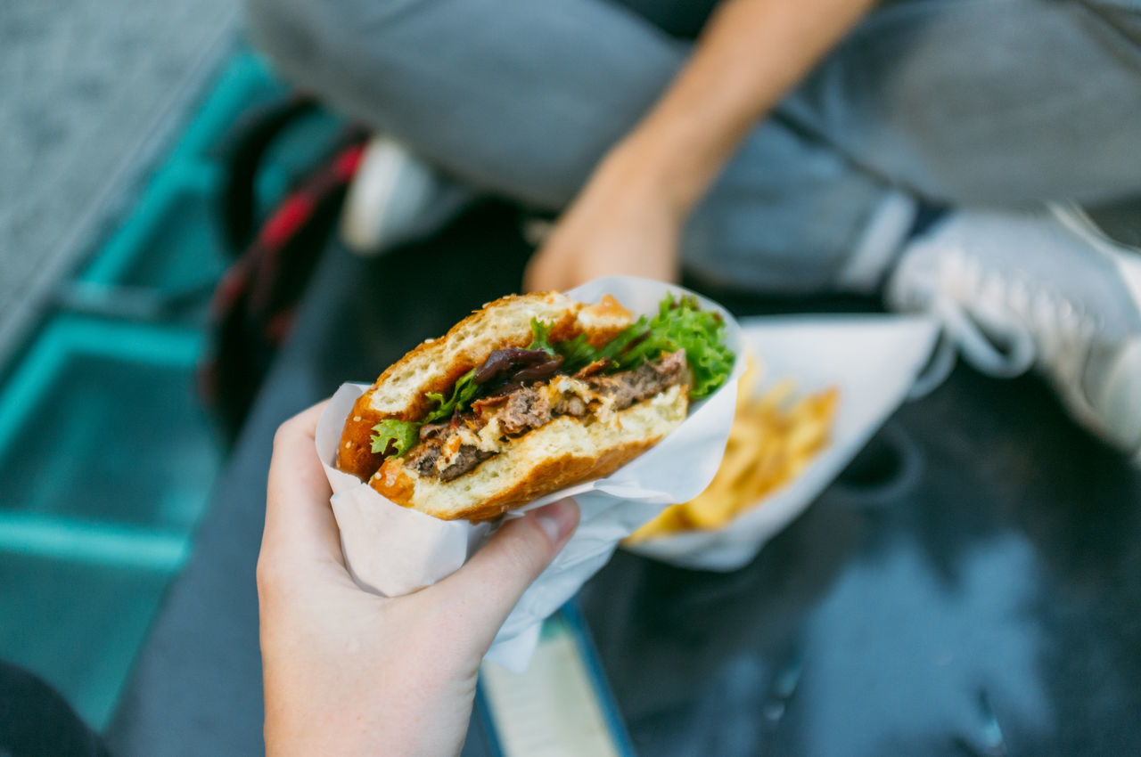 Cropped image of woman holding burger
