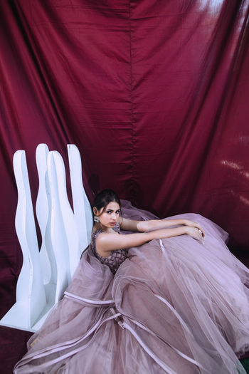 High angle portrait of woman wearing dress sitting against curtain