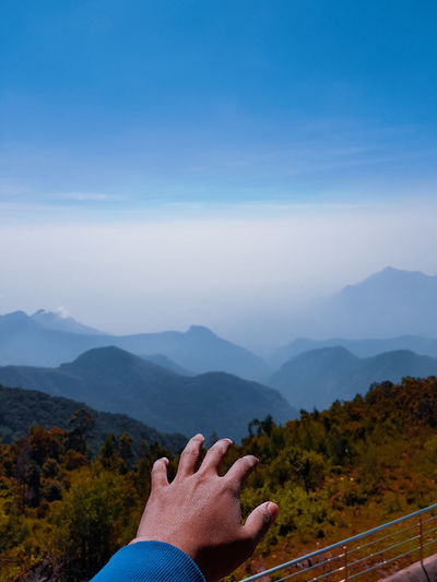 Cropped hand of person gesturing towards landscape against sky