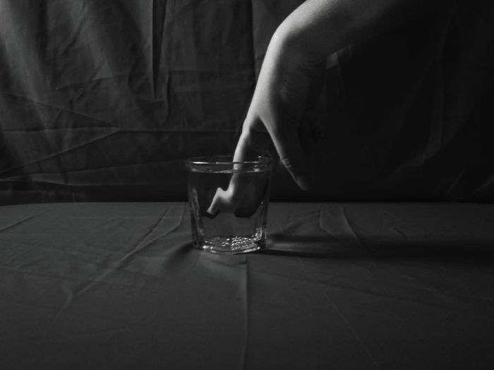 Close-up of woman hand in glass of water against black background