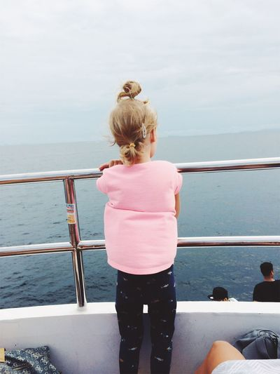Rear view of girl standing at boat deck