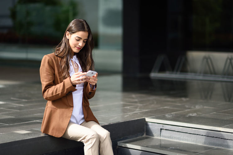 Young businesswoman using mobile phone while sitting on retaining wall