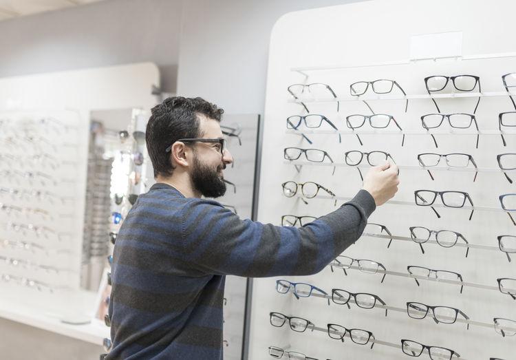 Smiling man looking eyeglasses in store