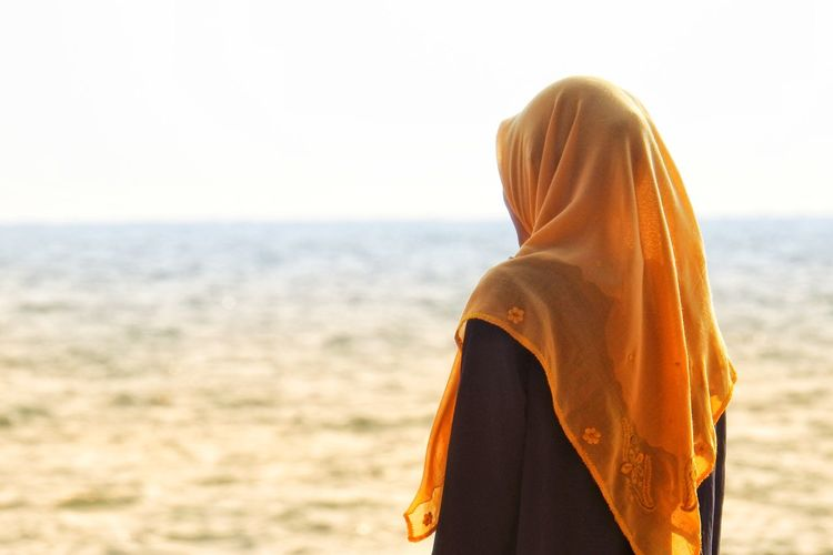 Side view of teenage girl wearing hijab standing at beach against clear sky