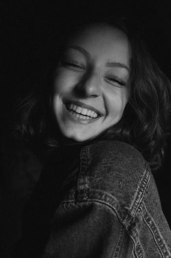 Close-Up Of Happy Young Woman Against Black Background