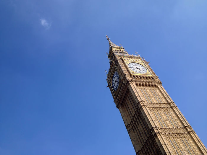 Low angle view of big ben against blue sky on sunny day in city
