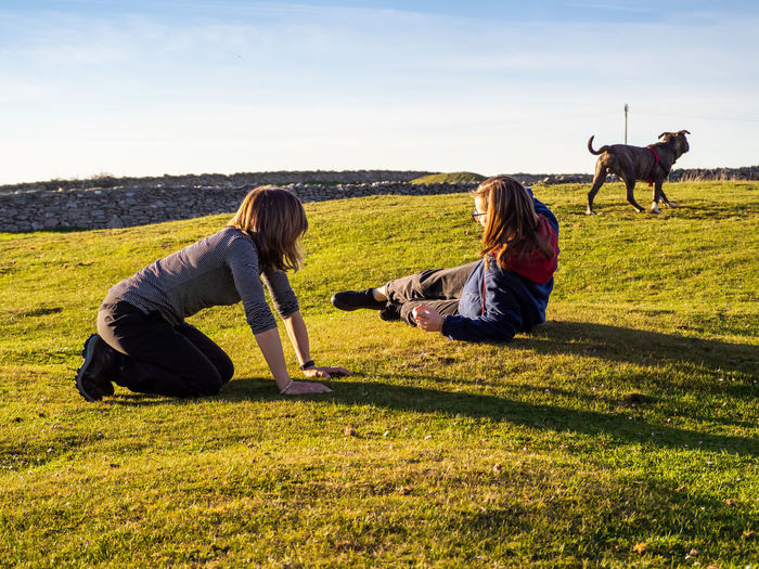 Girl and woman with dog on grass against sky