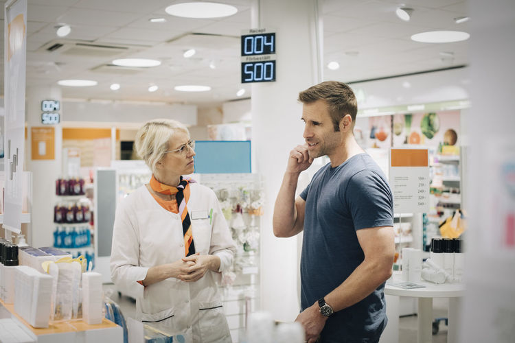 Full length of a man with woman standing in store