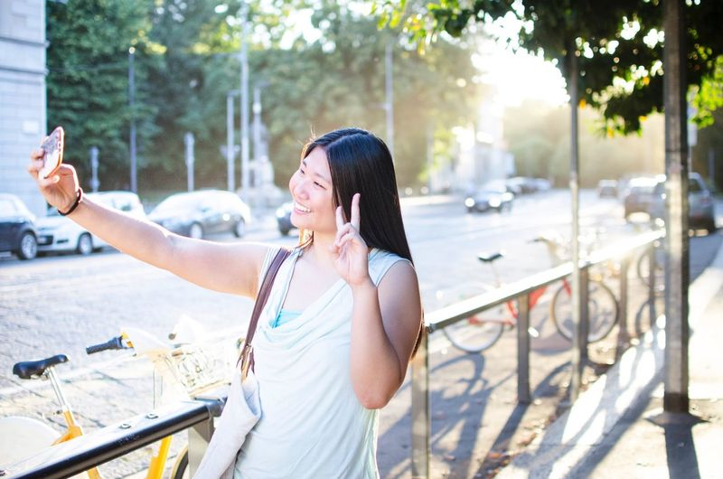 Woman gesturing while taking selfie through mobile phone on sidewalk
