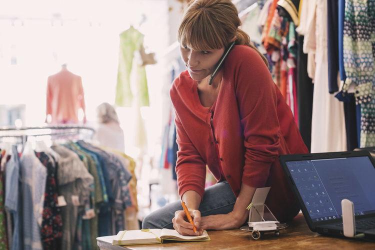 Senior woman using smart phone at store