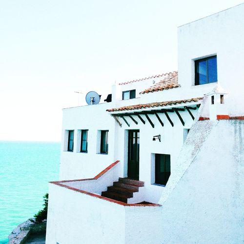 House by sea against clear sky