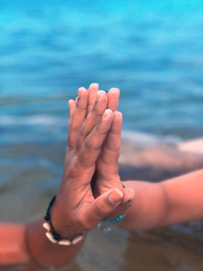 Close-up of couple hands over sea