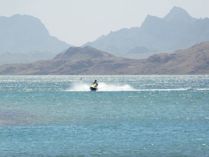 Person riding jet boat in sea against mountains