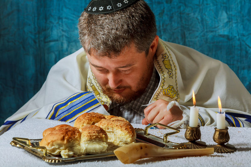 Man Looking At Breads In Plate By Lit Candles