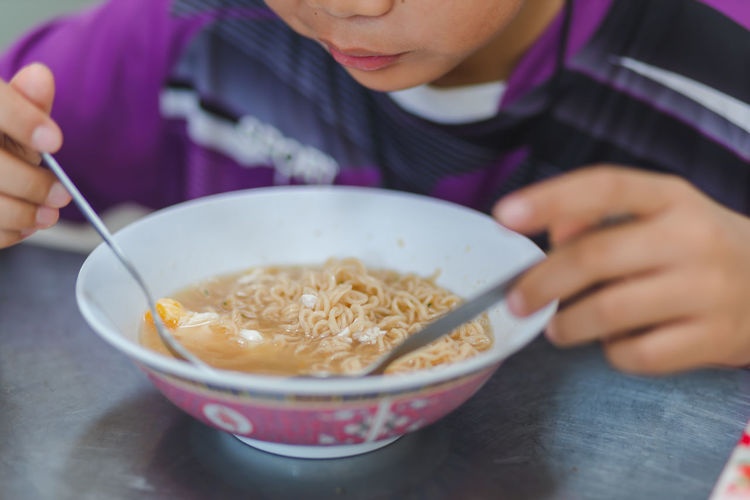 Midsection of man eating noodles in bowl