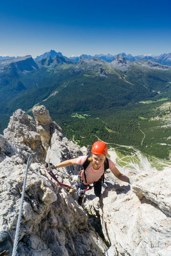 High angle view of woman climbing on mountain against clear blue sky