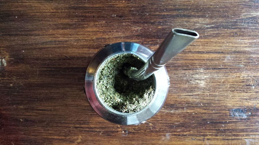 Directly Above Shot Of Yerba Mate In Container On Wooden Table