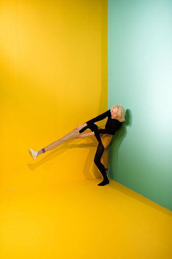 Woman Wearing Mannequin Leg While Standing Against Colored Background