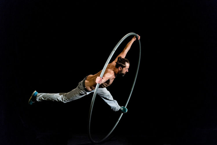 Circus Acrobat Agility Balance Black Background Copy Space Exercising Flexibility Full Length Gymnastics Healthy Lifestyle Holding Indoors  Lifestyles One Person Performance Skill  Sport Sports Clothing Strength Studio Shot Young Adult